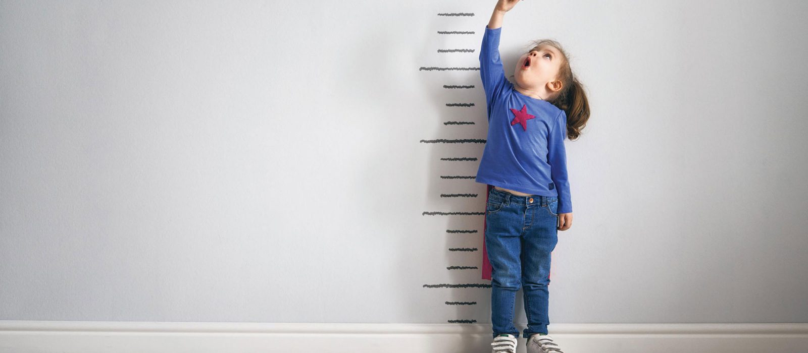 Girl measuring height against wall chart